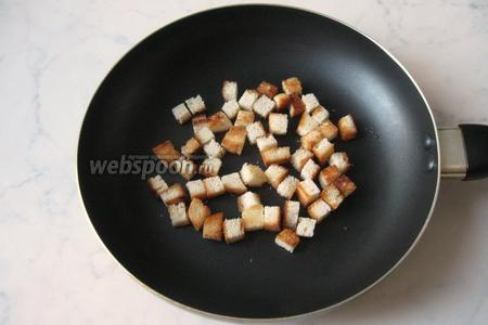 Обжарить кубики хлеба на сухой сковороде до образования золотистой корочки.
