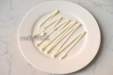 Формируем салат слоями. На большую, плоскую тарелку наносим сеточку майонеза.