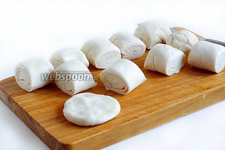 Слоёное тесто разморозить и плотно свернуть рулетом. Это делается для того, чтобы приблизить готовое тесто к приготовленному вручную, да и форма у самсы получится более традиционной. Рулет нарезать на одинаковые кусочки. Затем каждый кусочек приплюснуть в лепёшку.