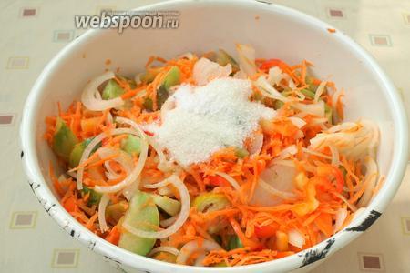 В глубокую миску выложить зелёные помидоры, добавить к ним перец, лук и морковь, всё перемешать. Влить подсолнечное масло, отмерять сахар и соль.