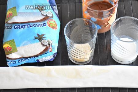 Для приготовления пирога с шоколадной пастой и кокосовой стружкой нам понадобится слоёное тесто, шоколадно-ореховая паста, кокосовая стружка, молоко и сахар.