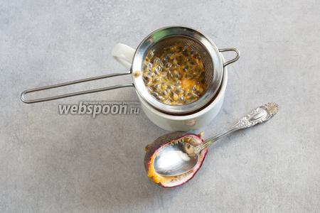 Разрежьте маракуйю на 2 половины, извлеките мякоть с зёрнами ложкой и протрите сок через металлическое ситечко.
