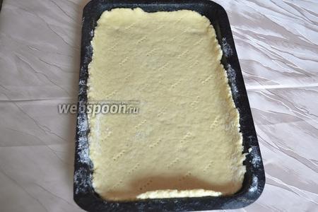Тесто разделите на 2 части и раскатайте на посыпанной мукой поверхности, по размеру формы. Противень посыпьте мукой, переложите 1 часть теста в форму и проколите в нескольких местах вилкой.