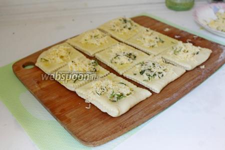 На квадраты теста присыпать сыр с розмарином.