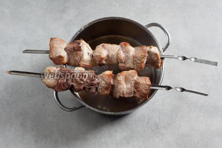 Шашлых запекаем приблизительно 20 минут (в духовке на верхнем уровне, на гриле), перевернув шампура 1-2 раза, по ходу дела сбрызнув вином. Над углями крутим и перекладываем так, чтобы мясо схватывалось равномерно, возможные возгорания тушим вином. Куски должны потемнеть, возможно, местами покоричневеть — но не чернеть. Критерий готовности — раздвинуть вилкой плотно прилегающие друг к другу куски шашлыка, если мясо внутри имеет пропечённый вид — значит, готово.