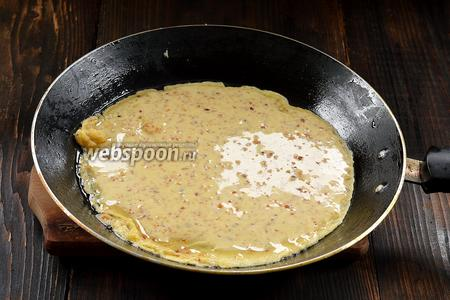 На горячую блинную сковороду тонким слоем налить тесто и распределить его по сковороде, наклоняя сковороду в разные стороны.