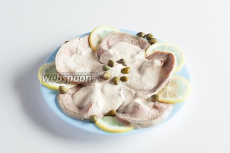 Перед самой подачей, к мясу с майонезом, на тарелку укладываются тонко нарезанные пластины лимона, а сверху посыпаются каперсы.