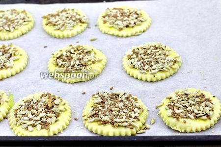 В отдельной посуде смешайте семечки, семена льна и кунжут. Посыпьте злаками смазанную поверхность. Отправьте в разогретую духовку на 25-35 минут при температуре 180°C.