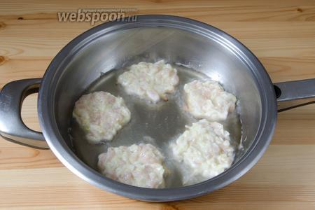 С помощью столовой ложки, выкладываем куриные оладьи с кабачком на сковороду с разогретым растительным маслом и обжариваем по 3-4 минуты с каждой стороны.