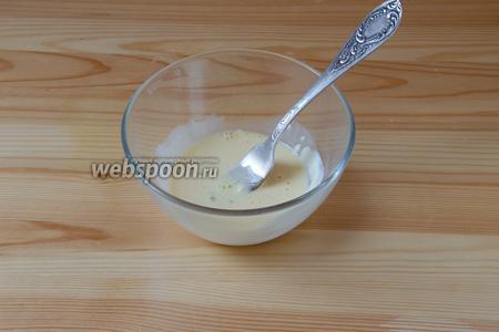 Подготавливаем смесь для смазывания поверхности хачапури. Для этого в миске смешиваем куриный желток и сметану. Благодаря этой смеси, у готовых хачапури получается красивый глянцевый верх.