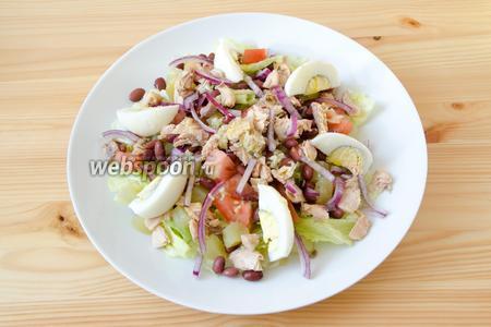 Выкладываем салат на порционные тарелки. Сначала кладем листья салата, затем фасоль и лук, а также помидоры и картофель. Добавляем горбушу и выкладываем по кругу яйца. Поливаем все сверху салатной заправкой и подаем к столу.