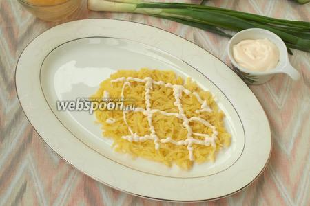 Сварить картофель, почистить и натереть на тёрке. Разделить картофель на 2 части. На овальное блюдо выложить слой картофеля в форме овала, так, чтоб 1/3 блюда осталась свободной. Сделать на картофеле сеточку из майонеза или аккуратно размазать его ложкой. Посолить картофель.