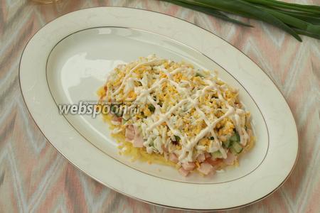 Яйца сварить, почистить и натереть на тёрке, разделить также пополам. Выложить 1 часть поверх огурца. Нанести майонезную сеточку.