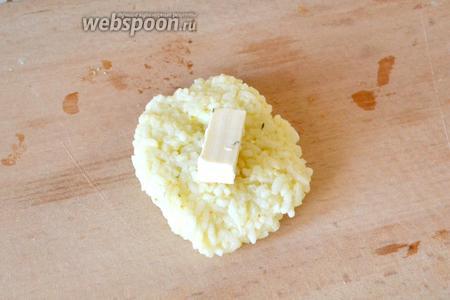 Отщипываем от рисовой массы кусок. Делаем из него лепёшку и кладём в серединку кусочек плавленого сыра.
