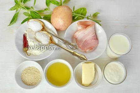 Берём картофель небольшого размера, оливковое масло,  соль, семена кунжута; для соуса — сливочное масло, муку, молоко, соль, сахар, перец чили, свежие листья базилика, йогурт; ещё возьмём бекон и зелень.
