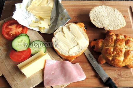 Разрезаем булочки на 2 половинки. Намазываем маслом и занимаемся нарезанием всех остальных составных начинки.