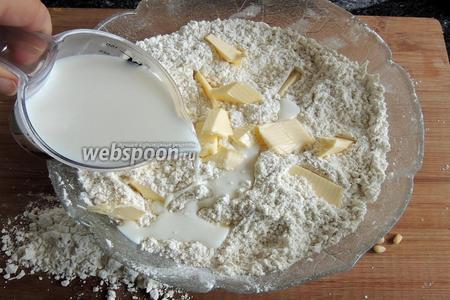 Сливочное масло, нарезанное малыми кусочками, добавим и вливаем молоко. Начинаем мешать изнутри наружу.