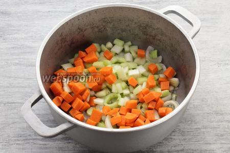 Следом добавляем кубиками нарезанные морковь и стебли молодого сельдерея, пропитываем маслом 2-3 минут.