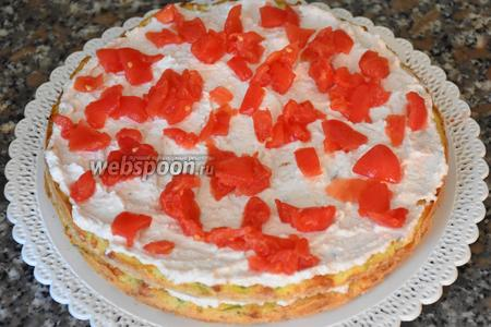 Сборка торта. На блюдо выложить корж, затем слой крема. Сверху выложить слой нарезанных помидоров.