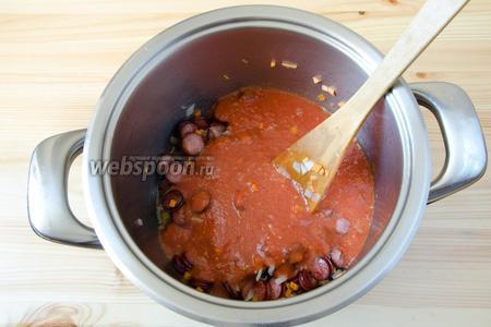 Когда лук и морковь немного размягчатся, отправляем в кастрюлю томатное пюре, перемешиваем и доводим до кипения.