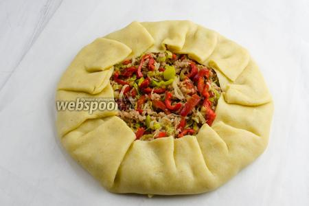 Завернуть тесто по краям равномерными складками, накрывая часть начинки. Центр начинки оставить открытым.