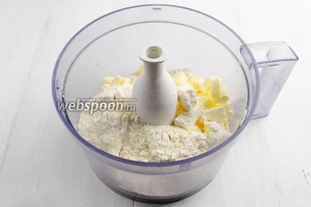 В чашу кухонного комбайна выложить нарезанное кусочками холодное масло, сахар, соль, муку.