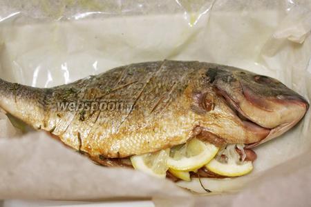 Промаслить пергамент и уложить рыбу в центр, в брюшко уложить дольки лимона и веточки тимьяна.