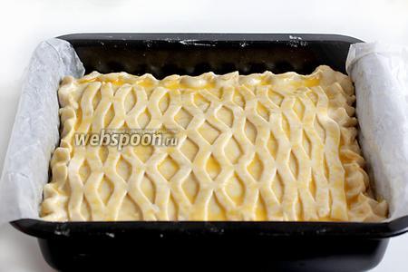 Накрыть второй частью теста, защипнуть края и украсить по своему желанию. Смазать поверхность взбитым яйцом. Выпекать пирог при 180°C до румяной корочки.