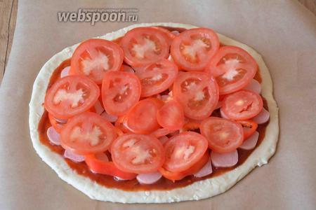 Тонкими кольцами порезать помидор, выложить сверху на сосиски.