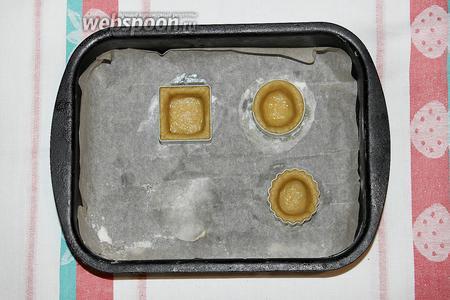 Аккуратно уложите тесто в формы. Разровняйте его по углам и стенкам. Излишки теста отрежьте ножом. Уберите заготовки в холодильник на 30 минут.