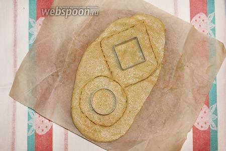 Положите форму для тарта на раскатанное тесто. Отмерьте от формы примерно 2-3 сантиметра. Вырежьте отмеренные формы.