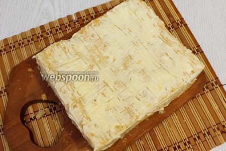 Сверху укладываем 3 корж слоёного теста, слегка прижимаем, обмазываем сыром. Убираем в холодильник для пропитки.