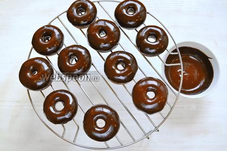 Переливаем шоколадный ганаш в миску, в которую будет удобно опускать пончики. Опускаем в шоколад пончик до половины его высоты и выкладываем на решётку. Видите, на решётке 11 пончиков, уже трудно было устоять, чтобы не попробовать один!