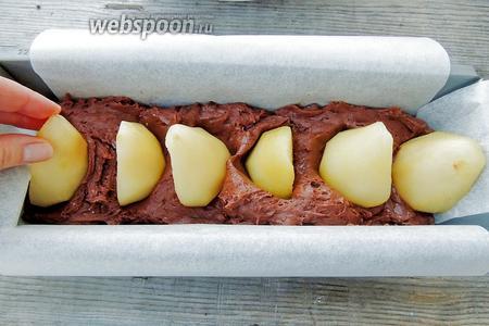В выстеленную бумагой кексовую форму выкладываем 1/2 теста. Втыкаем половинки груш.