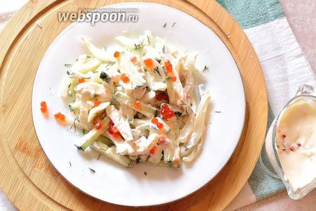Салат разложить по тарелкам и заправить сливочно-икорной смесью перед подачей. Сверху ещё немного посыпать красной икрой. Салат из кальмаров, с огурцом, зеленью и сливочно-икорной заправкой, готов.