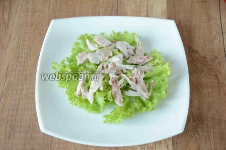 Куриное филе порезать средними кусочками. Выложить куриное филе на листья салата, посолить.