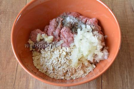 В глубокой миске соединить фарш, овсяные хлопья, измельчённый чеснок и репчатый лук, соль, перец чёрный молотый. Хорошо перемешиваем в однородную массу.