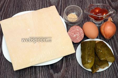 Для приготовления закуски с колбасой, кунжутом и огурцами вам понадобится тесто слоёное бездрожжевое, колбаса, кетчуп, майонез, кунжут, яйцо куриное, лук, огурцы солёные.