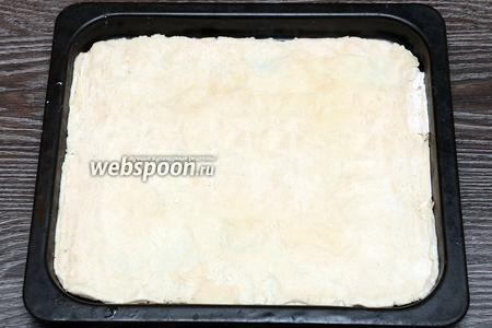 Раскатываем тесто по форме противня, можно просто растянуть его руками.