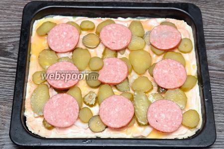 Раскладываем колбасу и мысленно делим противень на квадраты. Выливаем взбитое куриное яйцо прямо на тесто.