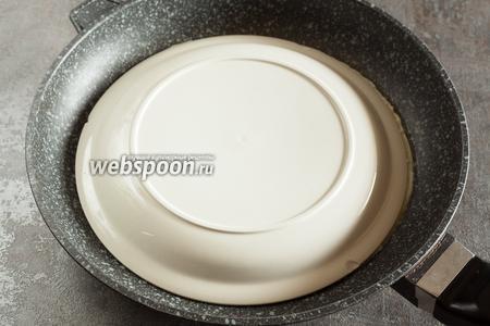 Когда омлет превращается во что-то вроде белой латексной массы, его накрывают тарелкой аналогичного диаметра и сковороду переворачивают.