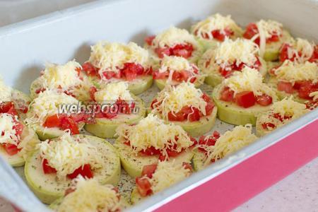 Посыпьте кабачки с помидорами сыром.