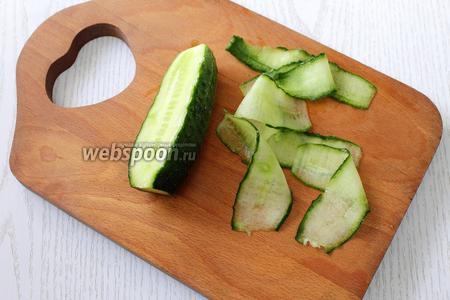 Нарезаем огурец тонкими слайсами при помощи тёрки для овощей.