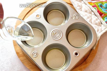 Минут через 10-15, достаём формы и наливаем на дно, в  каждую, немного масла и опять ставим в духовку. Нужно, чтобы масло очень хорошо прогрелось и было горячим (около 3 минут нужно). Пудинги очень поднимутся.