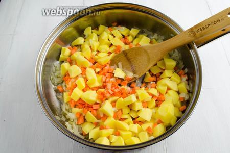 К луку добавить подготовленный картофель и морковь. Перемешать, 2 минуты подержать на среднем огне.