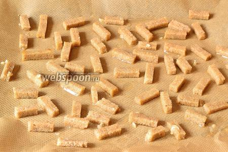 Затем все получившиеся кусочки ржаного хлеба обмокнуть в чесночном масле и выложить на противень. Поставить в разогретую до 120°С духовку на 25-30 минут. Периодически перемешиваем