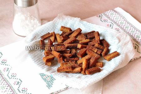 Вынимаем сухарики из духовки, выкладываем на салфетку, чтобы впиталось лишнее масло. Немного посолить и остудить.