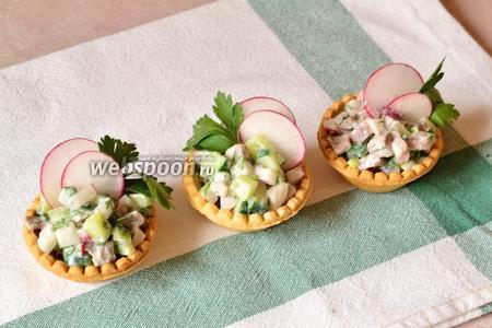 Разложить салат по тарталеткам. Украсить редисом и зеленью. Подаём на стол.
