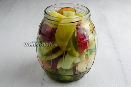 В стерилизованные банки выложить подготовленные помидоры, яблоки и стебли сельдерея.