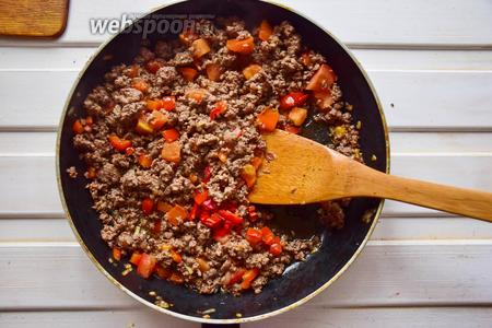 Выложим помидоры и перец к фаршу, перемешаем, при необходимости посолим и поперчим.